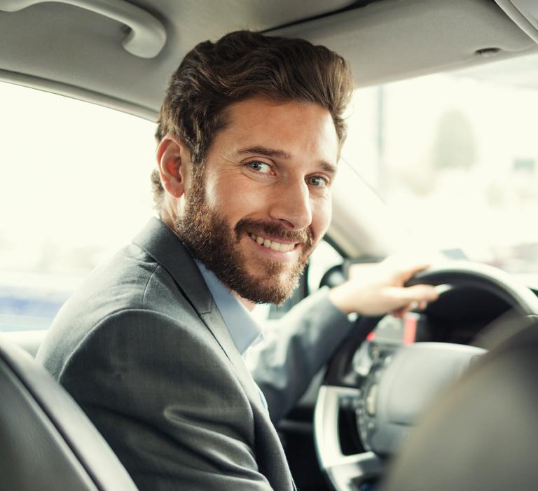 mężczyzna wgarniturze zakierownica samochodu